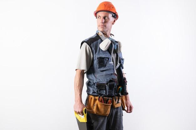 Der baumeister in einem helm und beim entladen hält eine bügelsäge in den händen an einem baum. auf hellem hintergrund. für jeden zweck.