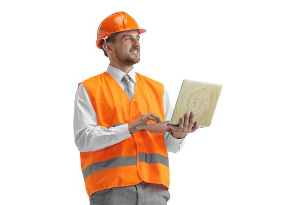 Der baumeister in einer bauweste und einem orangefarbenen helm mit laptop. sicherheitsspezialist, ingenieur, industrie, architektur, manager, beruf, geschäftsmann, jobkonzept