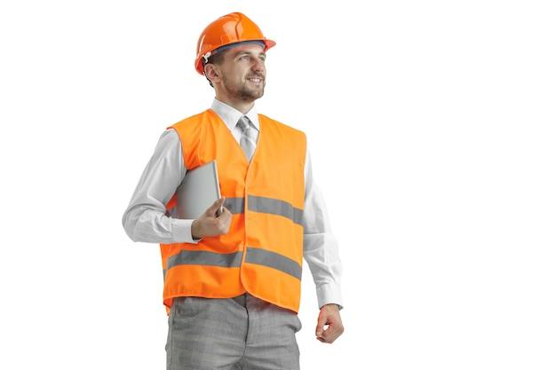 Der baumeister in einer bauweste und einem orangefarbenen helm mit tablette. sicherheitsspezialist, ingenieur, industrie, architektur, manager, beruf, geschäftsmann, jobkonzept