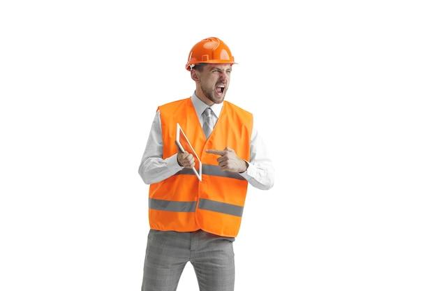 Der baumeister in einer bauweste und einem orangefarbenen helm mit tablette.