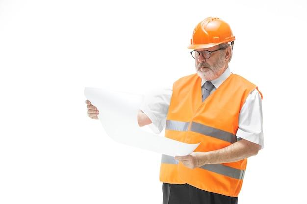 Der baumeister in einer bauweste und einem orangefarbenen helm steht auf einer weißen studiowand