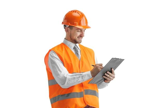 Der baumeister in einer bauweste und einem orangefarbenen helm steht auf weißer wand. sicherheitsspezialist, ingenieur, industrie, architektur, manager, beruf, geschäftsmann, jobkonzept