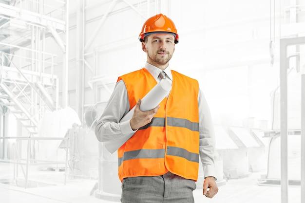 Der baumeister in einer bauweste und einem orangefarbenen helm steht. sicherheitsspezialist, ingenieur, industrie, architektur, manager, beruf, geschäftsmann, jobkonzept