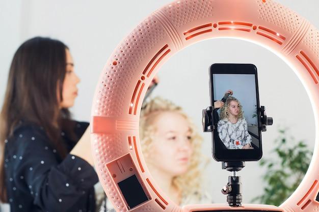 Der beauty-blogger zeichnet den make-up-prozess bei einer schönen blondine auf