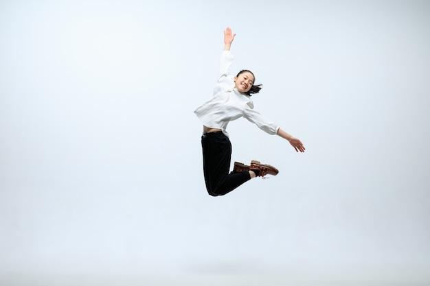 Der beginn des neuen lebens. glückliche frau, die im büro arbeitet, springend und tanzend in der freizeitkleidung oder im anzug lokalisiert auf weißem studiohintergrund. business, start-up, funktionierendes open-space-konzept.