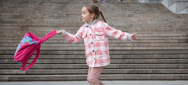 Der beginn des unterrichts und der erste tag des herbstes. ein süßes mädchen steht auf einer großen breiten treppe.