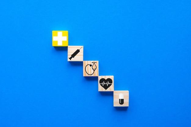Der begriff der krankenversicherung, kopienraum auf einem blauen holzwürfel mit medizinischen symbolen des gesundheitswesens auf blauem hintergrund.