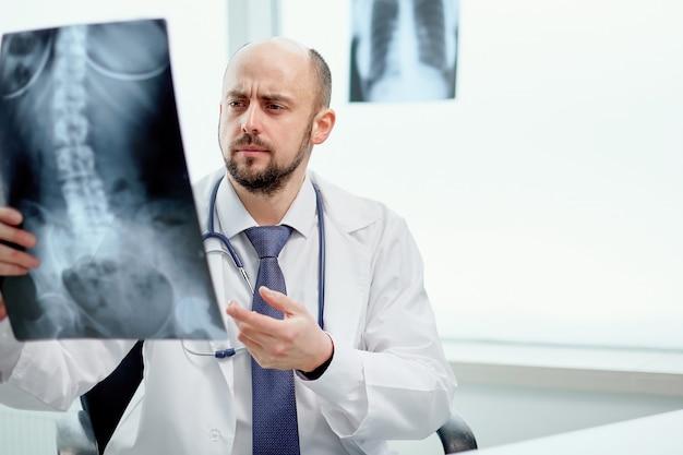 Der behandelnde arzt zeigt auf eine röntgenaufnahme seines patienten