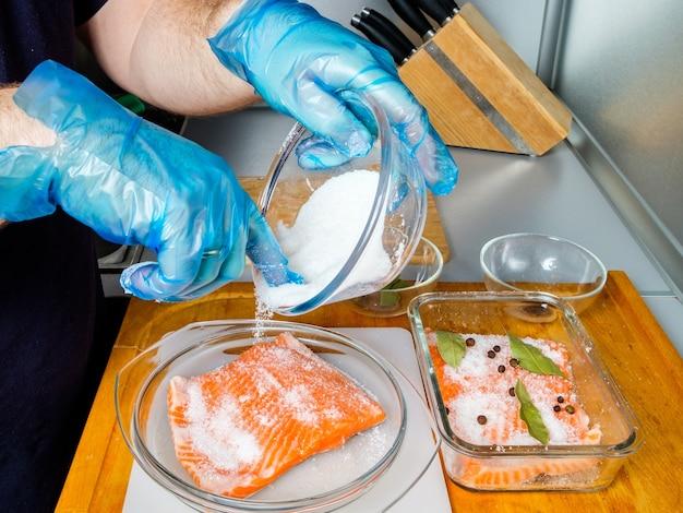 Der behandschuhte koch bestreut das lachsfilet mit pökelmasse