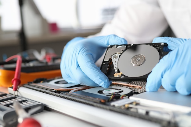 Der behandschuhte meister hält eine festplatte. diagnose und reparatur des computerausrüstungskonzepts