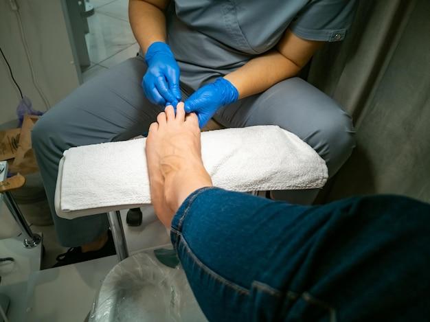 Der behandschuhte meister macht eine pediküre für eine kundennahaufnahme ohne gesicht frau in einem nagelstudio lackiert ihre nägel