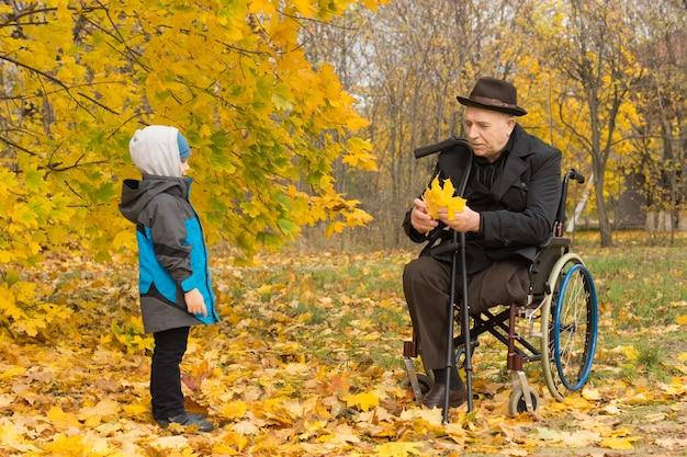 Der behinderte großvater ist an einen rollstuhl gebunden und spielt mit seinem süßen kleinen enkel
