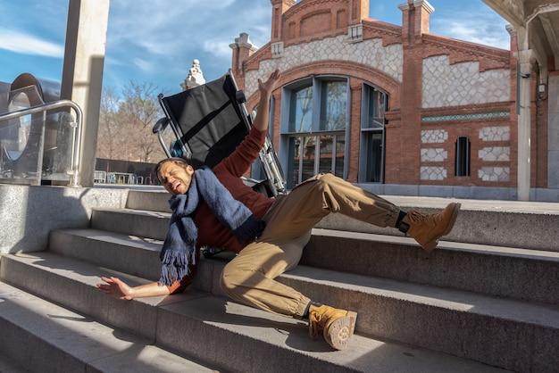 Der behinderte junge latino-mann im rollstuhl fällt eine treppe hinunter, die er mit dem stuhl auf der straße nicht hinuntergehen kann