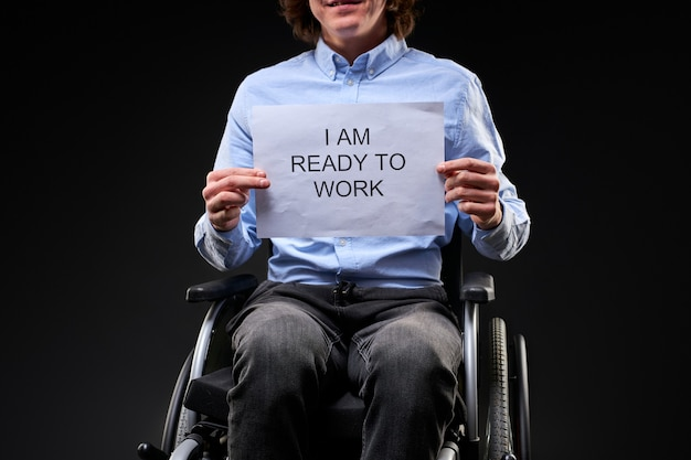 Der behinderte mann sucht einen job, der kaukasische junge mann sitzt im rollstuhl und braucht einen job. er ist bereit zu arbeiten. trotz behinderung