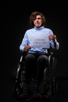 Der behinderte mann sucht einen job, der kaukasische junge mann sitzt im rollstuhl und braucht trotz behinderung einen job