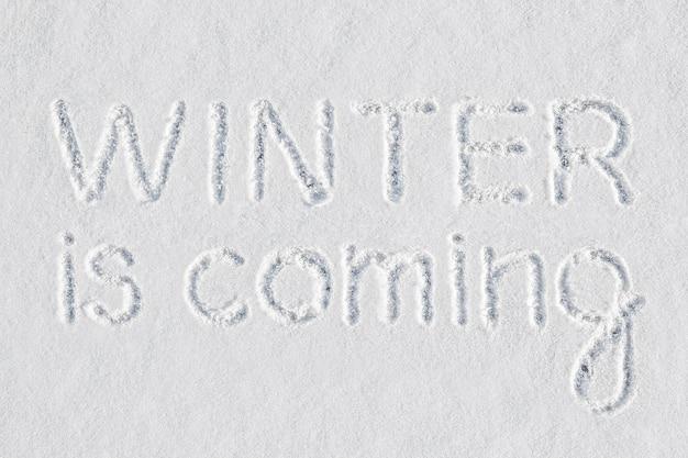 Der bekannte ausdruck winter is coming mit dem finger auf neuschnee geschrieben bedeutet, dass die kalte jahreszeit am ende des herbstes und am vorabend der winterferien naht.