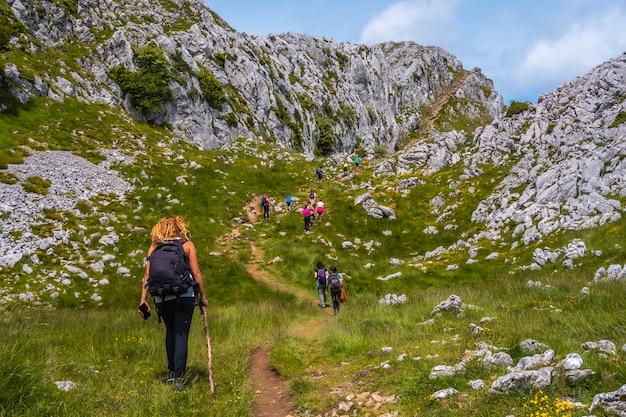 Der berg aizkorri ist 1523 meter hoch und der höchste in guipuzcoa. baskenland. junge blonde frau, die den harten aufstieg nach oben beginnt. steigen sie durch san adrian und kehren sie durch die oltza-felder zurück