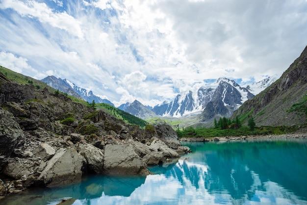 Der bergsee ist umgeben von großen steinen und felsbrocken vor einem riesigen, wunderschönen gletscher. erstaunliche schneebedeckte berge. grat mit schnee. wunderbare atmosphärische landschaft von majestätischer natur des hochlands.