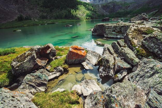 Der bergsee ist von großen steinen und felsen mit moosen umgeben