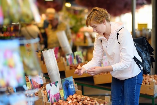 Der berühmte amsterdamer blumenmarkt (bloemenmarkt). reife frauen wählen tulpenzwiebeln.