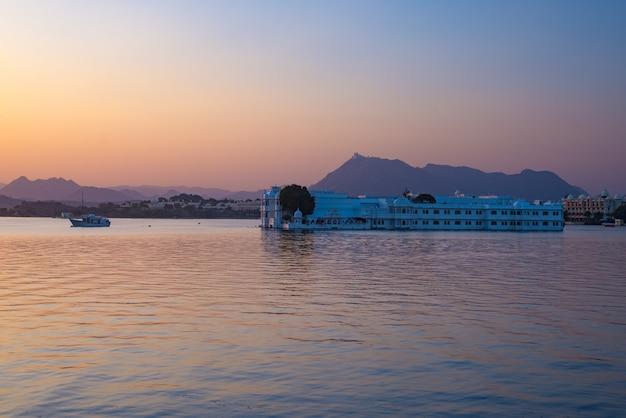 Der berühmte weiße palast, der auf see pichola bei sonnenuntergang schwimmt. udaipur, reiseziel und touristenattraktion in rajasthan, indien