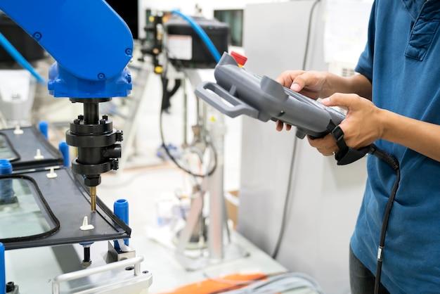Der berufsoffizier bringt dem roboter bei, indem er das steuerpaneel an das glas auf der trägerbasis anwendet