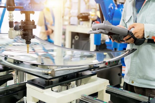Der berufsoffizier prüft den roboter, der sich auf das glas auf der trägerbasis bewegt.