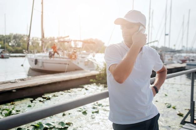 Der beschäftigte junge mann steht auf dem pier und schaut nach links. er telefoniert
