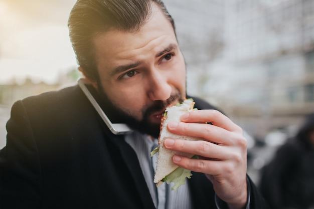 Der beschäftigte mann hat es eilig, er hat keine zeit, er wird unterwegs einen snack essen. arbeiter essen, kaffee trinken, gleichzeitig telefonieren. geschäftsmann, der mehrere aufgaben erledigt.