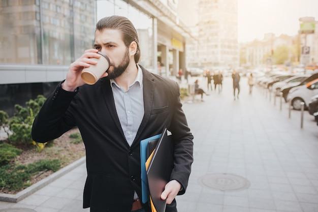 Der beschäftigte mann hat es eilig, er hat keine zeit, er wird unterwegs telefonieren. geschäftsmann, der mehrere aufgaben auf der motorhaube des autos erledigt. multitasking-geschäftsperson trinkt kaffee