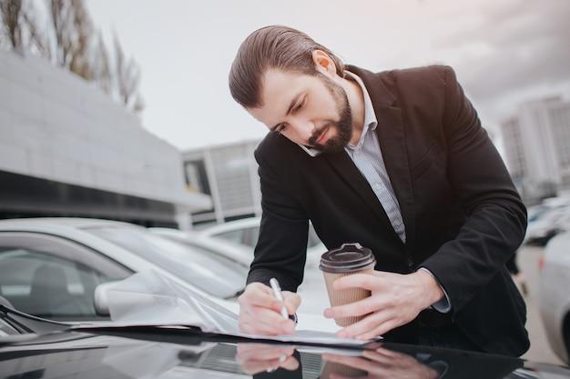Der beschäftigte mann hat es eilig, er hat keine zeit, er wird unterwegs telefonieren. geschäftsmann, der mehrere aufgaben erledigt der verkauf von autos, der käufer oder verkäufer ist das ausfüllen von leeren formularen auf dem auto.