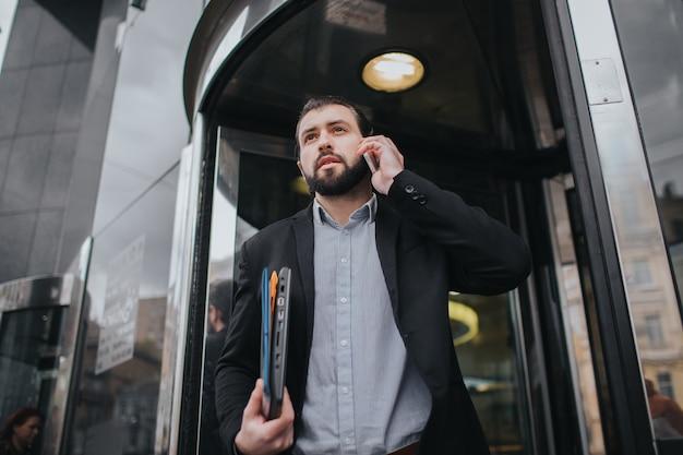 Der beschäftigte mann hat es eilig, er hat keine zeit, er wird unterwegs telefonieren. geschäftsmann, der mehrere aufgaben erledigt. multitasking-unternehmer.