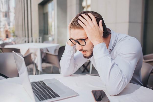 Der beschäftigte und unglückliche junge mann schaut näher auf den bildschirm des laptops. er hält die hände auf dem kopf. guy ist erstaunt. da ist sein telefon am tisch.