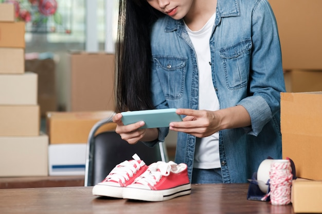 Der besitzer des online-verkäufers macht ein foto des produkts zum hochladen in den online-shop der website. online-verkauf, online-shopping und e-commerce-konzept.