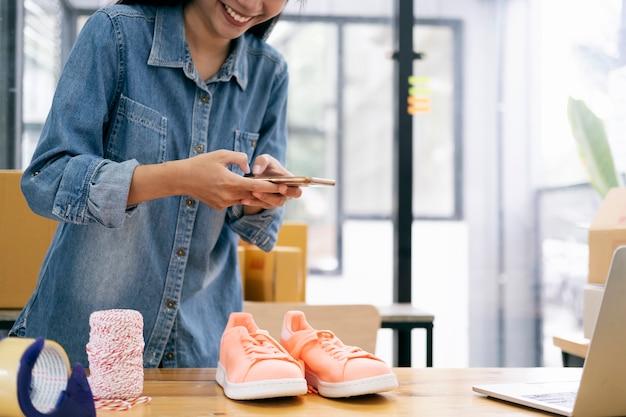 Der besitzer eines online-verkäufers macht ein foto des produkts, um es in den online-shop der website hochzuladen.