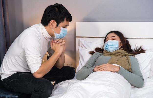 Der besorgte ehemann kümmert sich um seine kranke frau, während sie zu hause im bett schläft. die menschen müssen eine medizinische maske tragen, die vor einer coronavirus-pandemie schützt