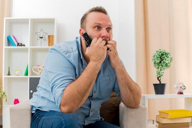 Der besorgte erwachsene slawische mann sitzt auf dem sessel und hält die fernbeißenden finger des fernsehers und schaut auf die seite im wohnzimmer