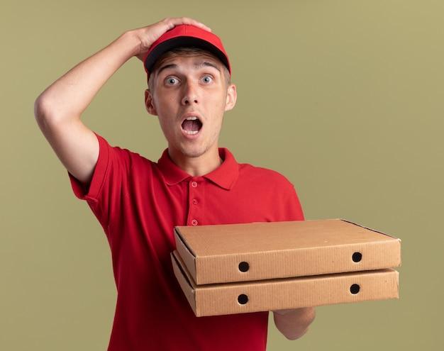 Der besorgte junge blonde bote legt die hand auf den kopf und hält die pizzaschachteln auf olivgrün