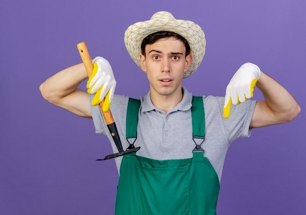 Der besorgte junge männliche gärtner, der gartenhut und handschuhe trägt, hält rechen und zeigt mit zwei händen nach unten