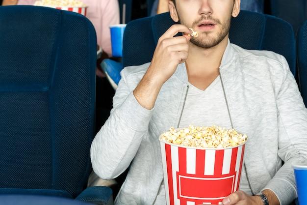 Der beste snack fürs kino. geernteter schuss eines mannes, der popcorn in einem kino isst