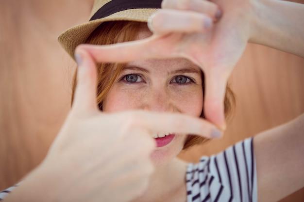 Der blauäugige hippie, der durch ihre hände schaut, mögen eine kamera