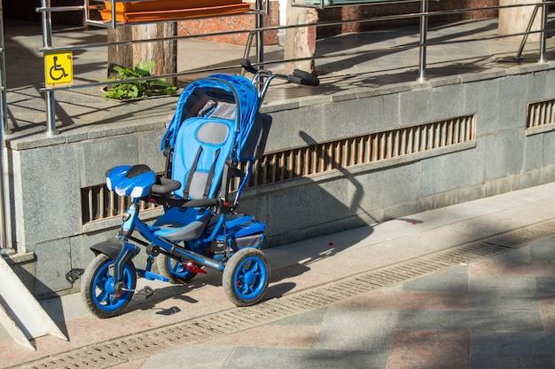 Der blaue dreiradspaziergänger der kinder steht auf dem parkplatz in der nähe eines supermarktes leer