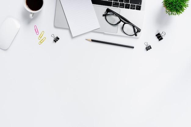 Der blaue schreibtisch und die ausrüstung des büros für das arbeiten in der draufsicht und in der ebene legen auf weißen hintergrund