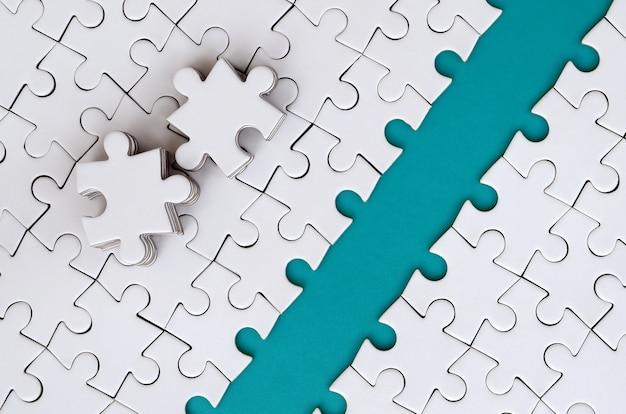 Der blaue weg wird auf die plattform eines weißen, gefalteten puzzles gelegt