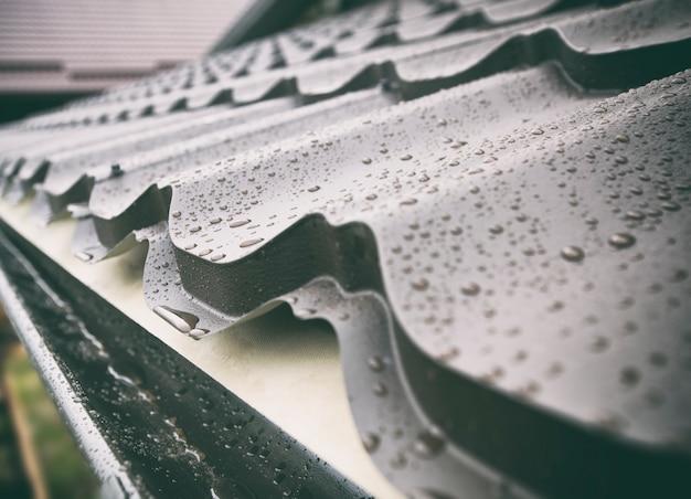 Der blick auf das nasse dach aus metallfliesen