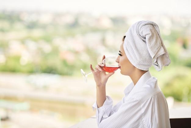 Der blick aus dem hotelfenster auf ein mädchen, das sich im bademantel mit einem weißen glas wein entspannt, raucht eine zigarette