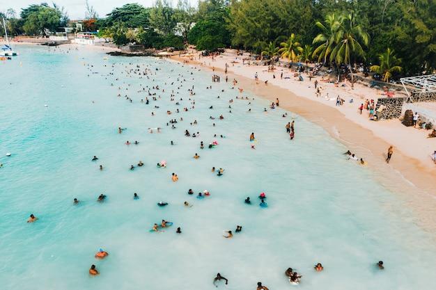 Der blick aus der vogelperspektive auf das meer, gefüllt mit menschen an einem heißen sonnigen tag. menschen schwimmen im indischen ozean auf der insel mauritius.