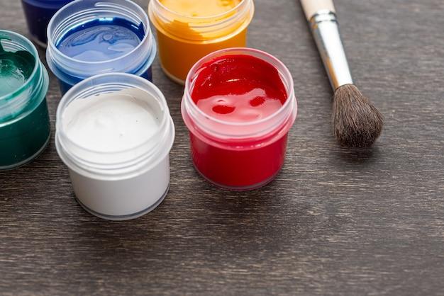 Der blick hinunter auf drei offene farbdosen mit farbiger farbe, die auf einem schäbigen holzboden standen