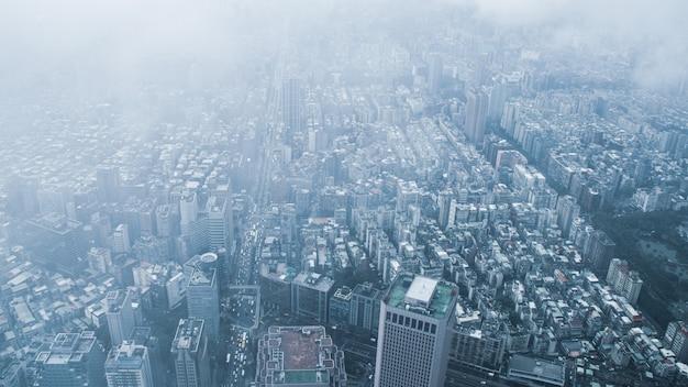 Der blick über taipeh, die hauptstadt taiwans, von der spitze von taipeh 101, dem zweitgrößten gebäude der welt, schießt nach regen mit nebel.