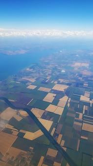 Der blick vom flugzeugfenster auf den boden. landschaftsansicht vom himmel.